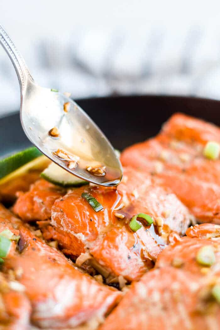 spoon drizzling honey glaze over baked salmon in a skillet