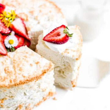 a piece of gluten free angel food cake being pulled off a platter with strawberries and whipped cream on top