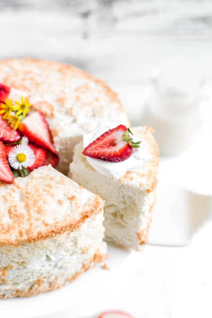 gluten free angel food cake recipe being removed from the cake with a strawberry on top
