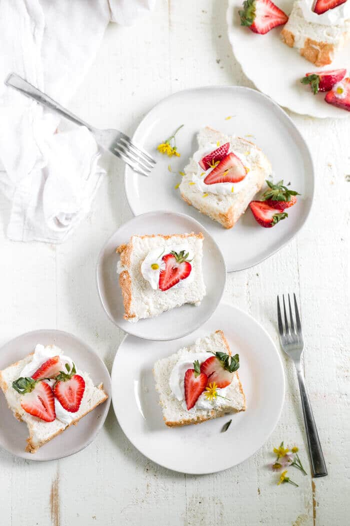 overhead shot of four plates with a piece of gluten free angel food cake on each topped with berries and cream