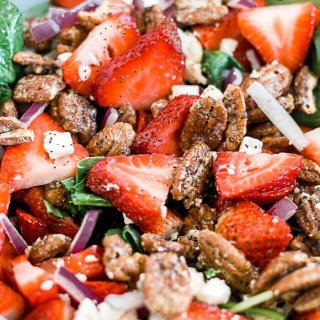 strawberry spinach salad tossed with healthy poppyseed dressing in a large white bowl