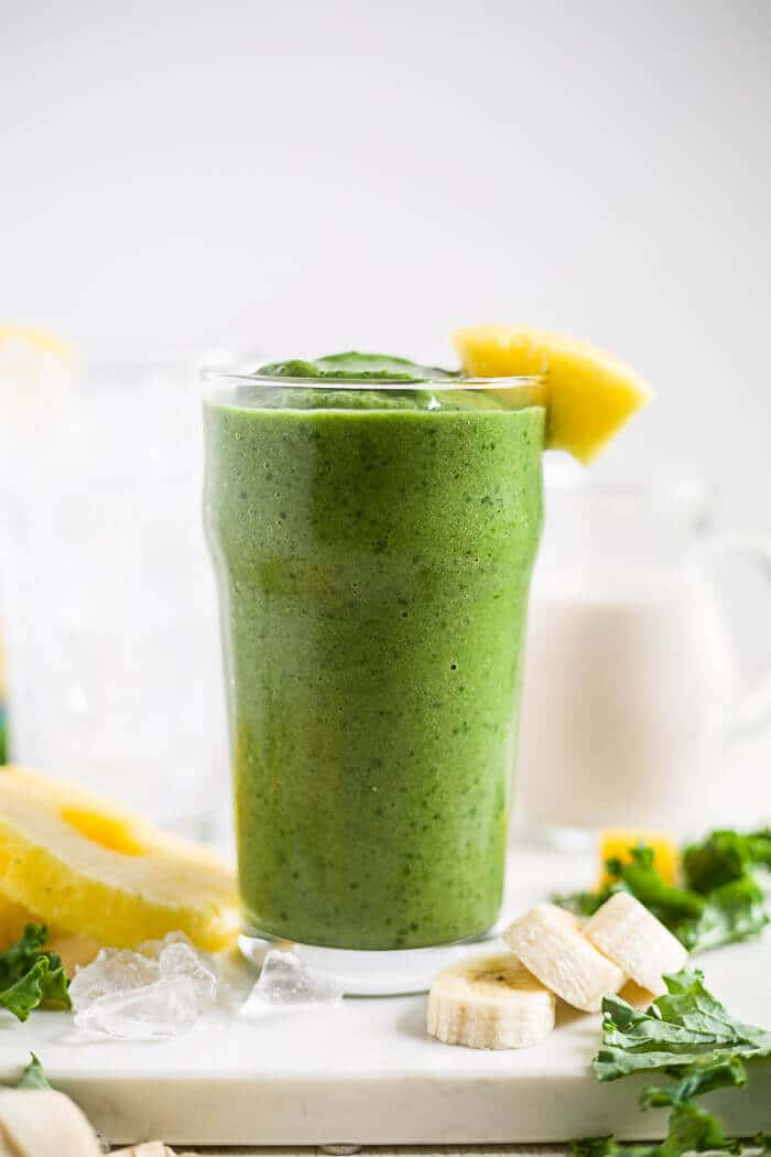 kale smoothie in a tall glass with pineapple
