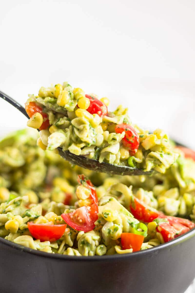 spoon scooping up creamy avocado pasta salad out of a bowl
