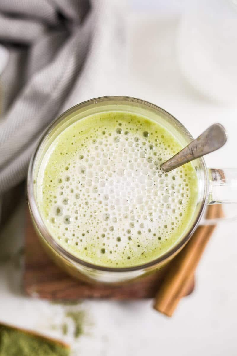 hot collagen matcha latte  in a clear mug with froth on the top