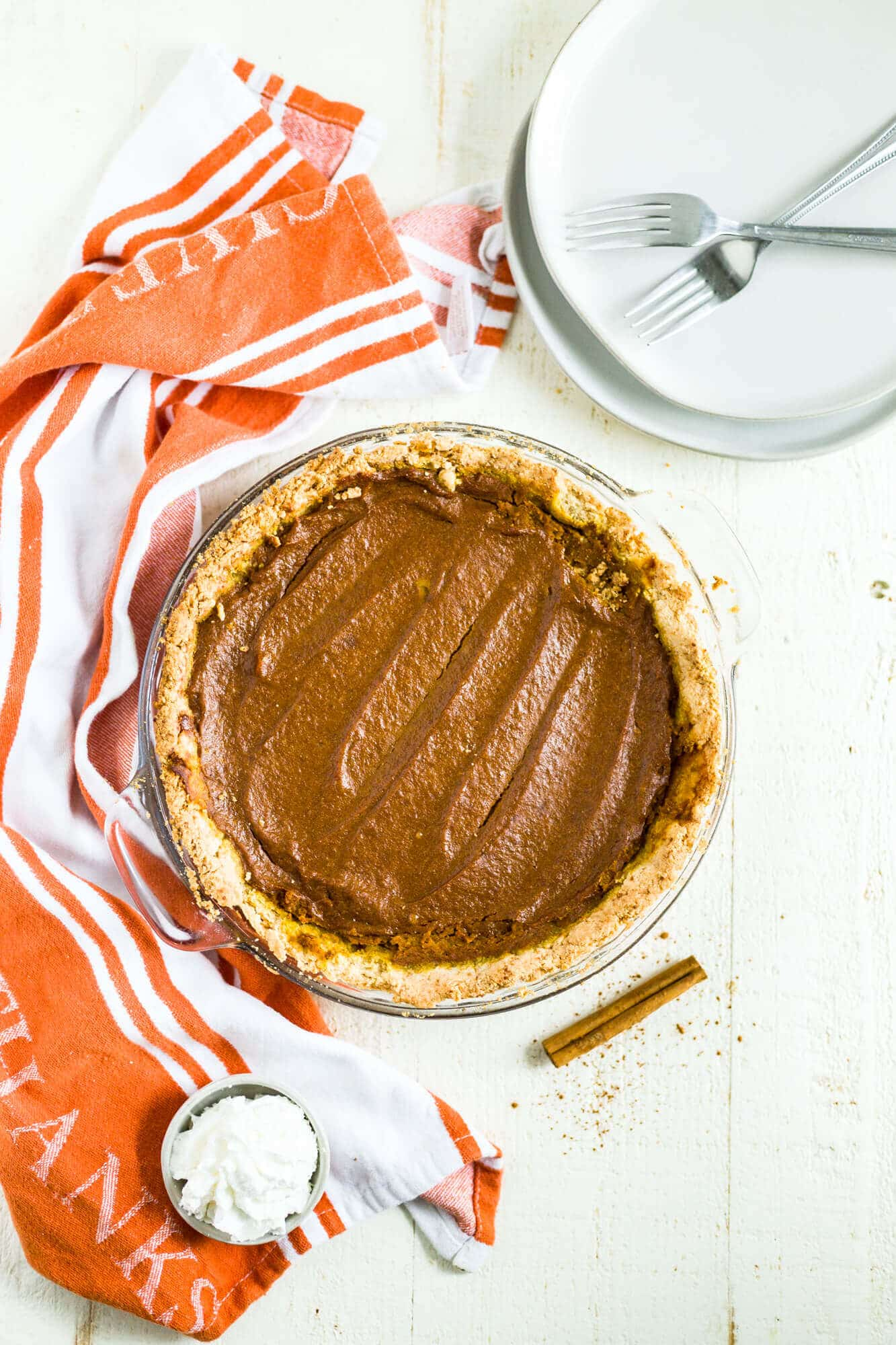 gluten free dairy free pumpkin pie in a glass pie dish with a few forks and orange and white dish towel