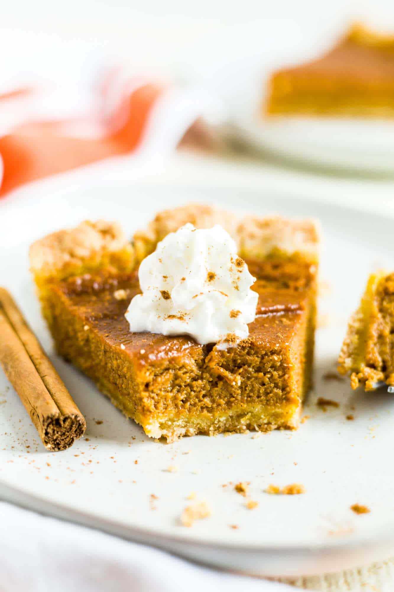 dairy free pumpkin pie on a white plate with coconut whipped cream and a bite taken out