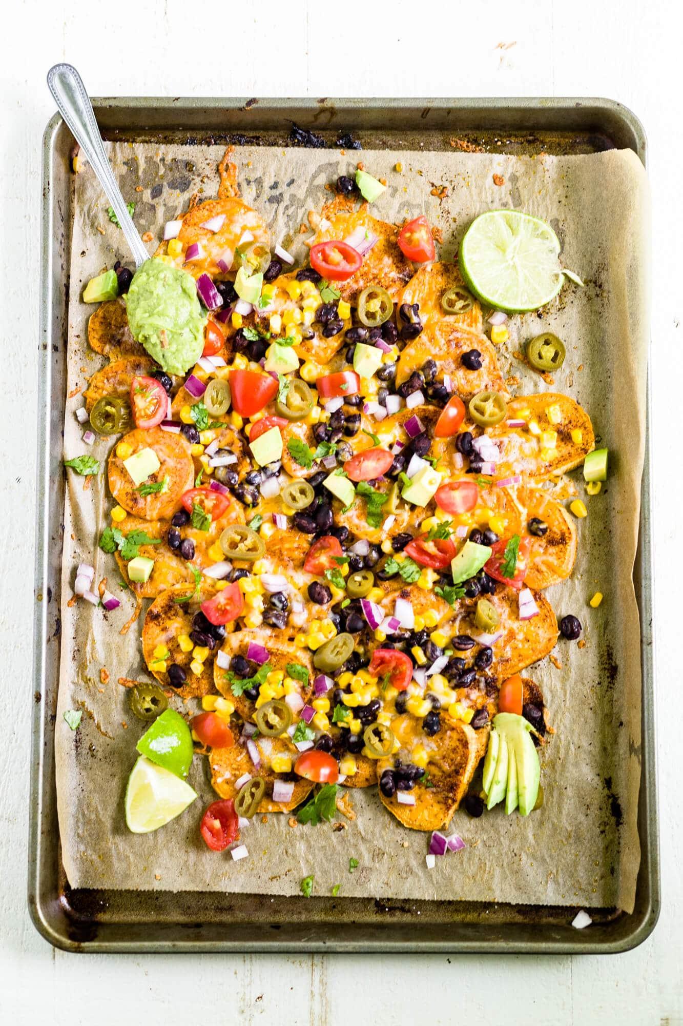 sweet potato nachos on a sheet pan topped with jalapenos, corn, beans, avocado, tomatoes and cilantro