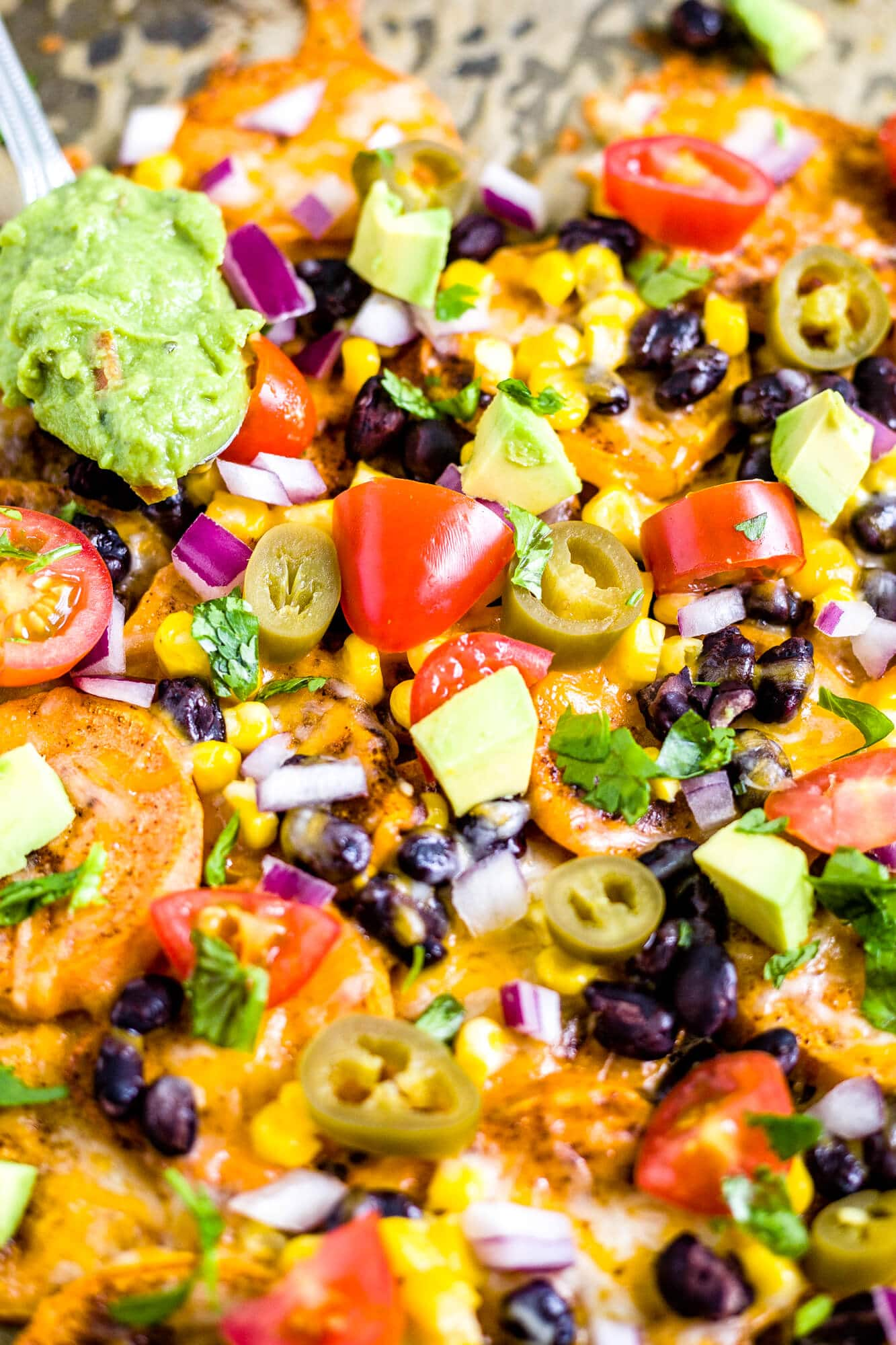recipe for sweet potato nachos loaded with mexican toppings and a dollop of guacamole