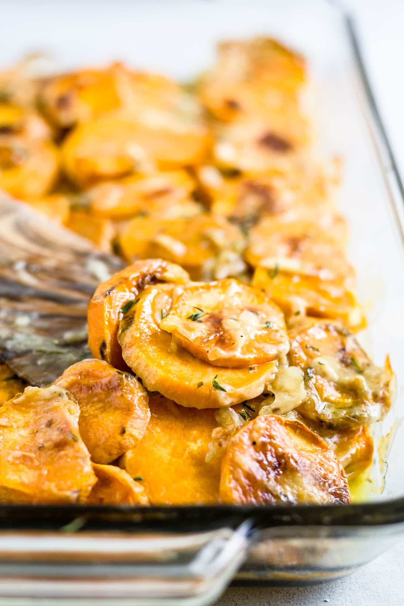 healthy scalloped sweet potatoes in a glass baking dish topped with fresh herbs