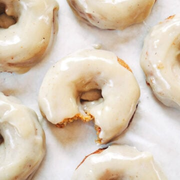 paleo pumpkin donuts on parchment paper with maple icing
