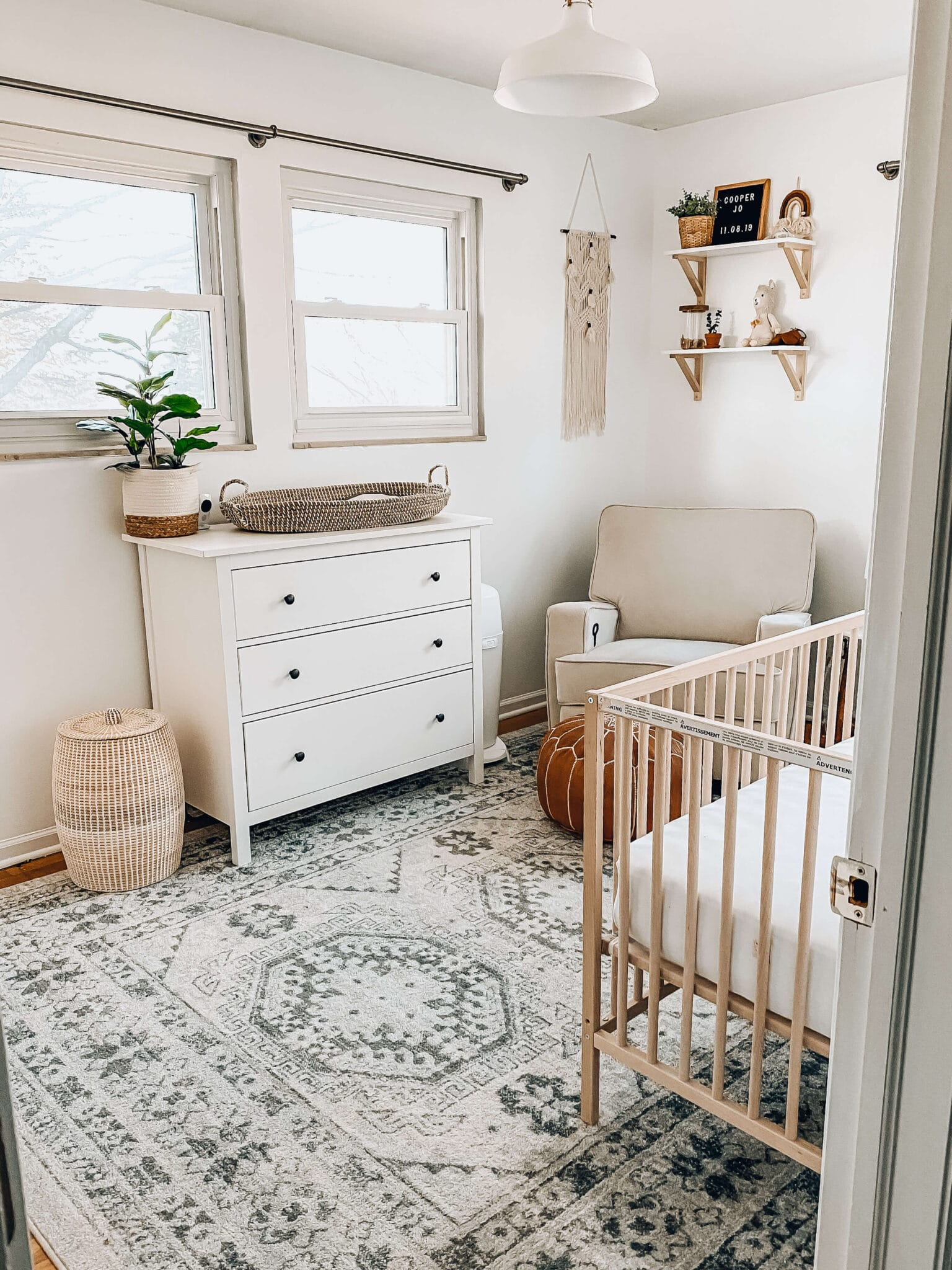 picture of neutral boho nursery with natural wood crib, white dresser, boho rug, and boho accents