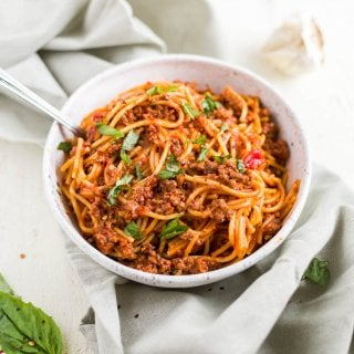 instant pot spaghetti in a white bowl with fresh basil