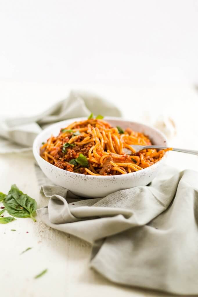 instant pot spaghetti in a bowl with fresh basil and a fork and napkin