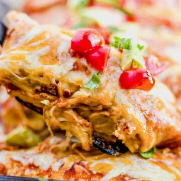 spatula scooping out healthy chicken enchiladas from a baking dish