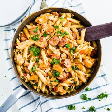 one pot creamy cajun chicken pasta in a pan on a kitchen towel
