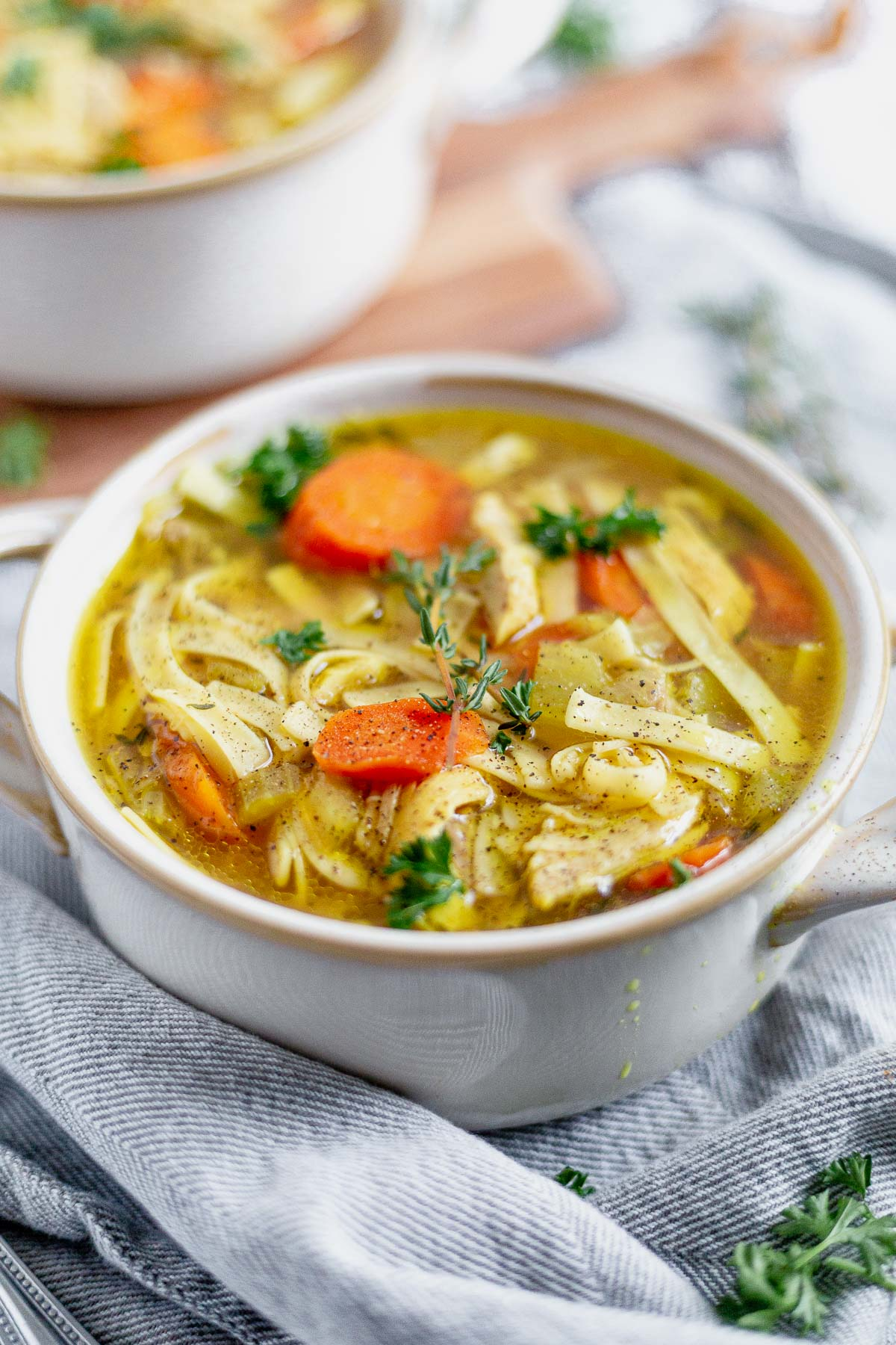 two bowls of instant pot chicken noodle soup on a grey napkin topped with parsley