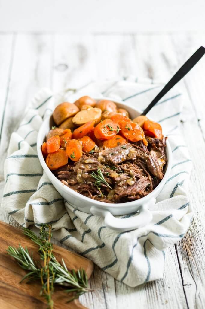 instant pot roast in a white bowl with a black serving spoon ready to be served