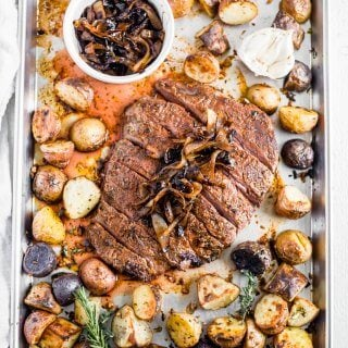 flank steak recipe on sheet pan with herbs, garlic, potatoes and caramelized onion