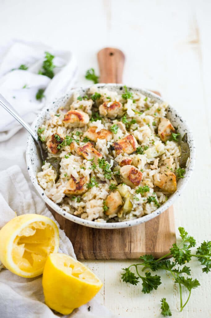 instant pot greek chicken and rice in a bowl with fresh lemon and parsley