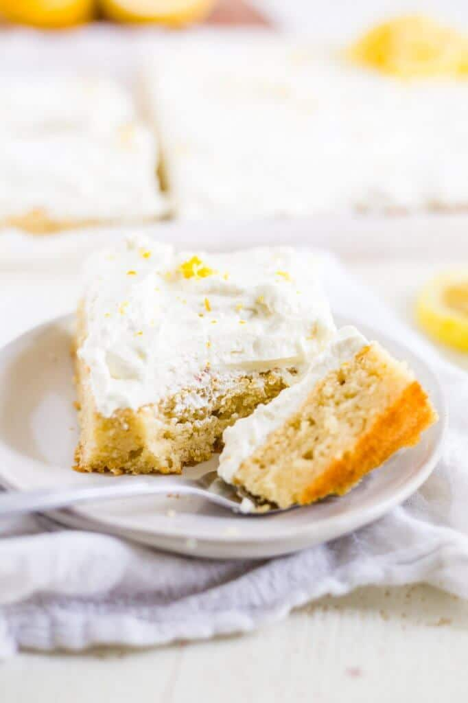 a slice of healthy lemon cake on a white place with a bite taken out with a fork