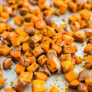 cubed sweet potatoes roasted with olive oil and fresh rosemary on a sheet pan