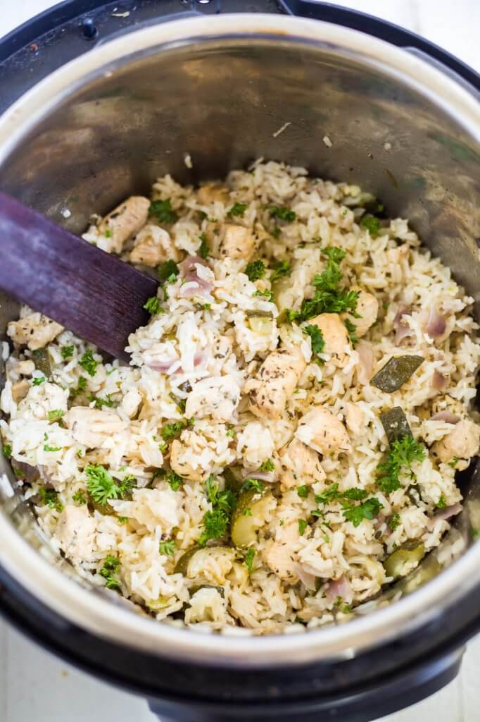 green chicken and rice in the instant pot with a wooden spoon