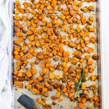 overhead shot of roasted rosemary sweet potatoes on a large metal sheet pan