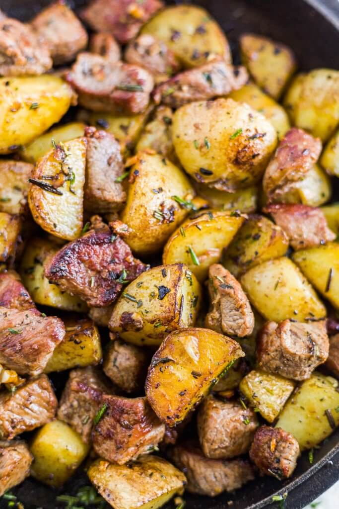 close up up crispy potatoes and steak bites with fresh herbs