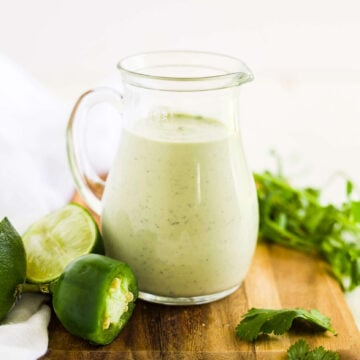 cilantro lime dressing in a glass jar on a wood cutting board