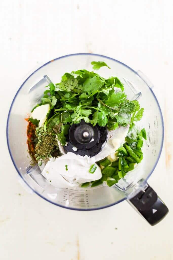 ingredients for cilantro lime dressing in a food processor before it's blended
