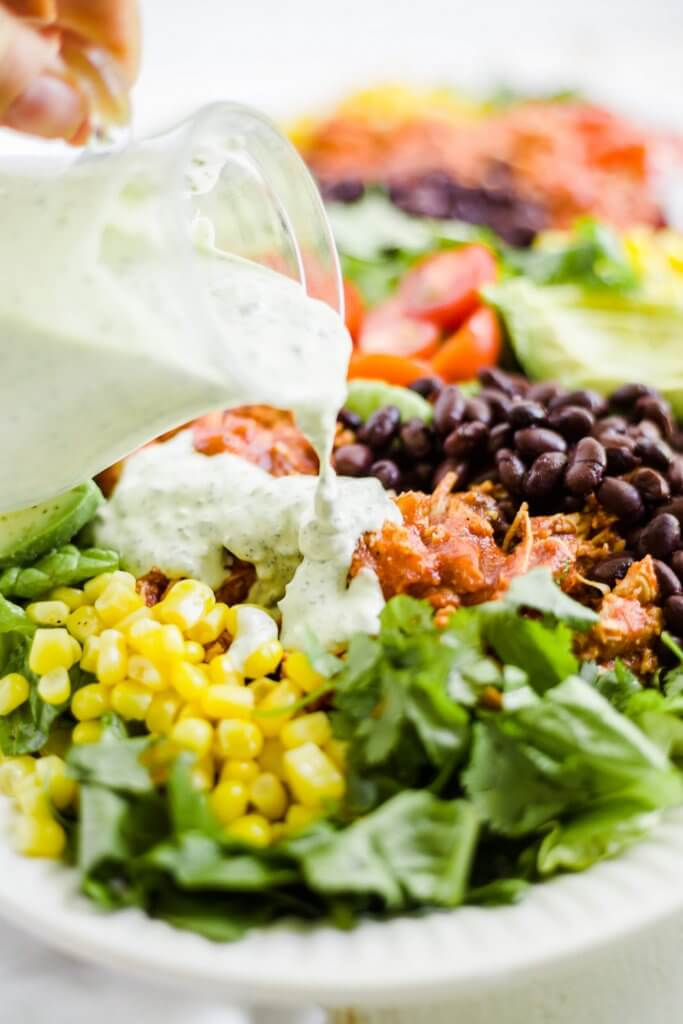 cilantro lime dressing being poured on a fiesta salad