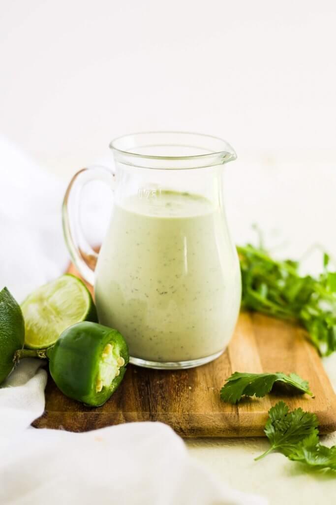 cilantro lime ranch dressing in a glass jar on a wood cutting board