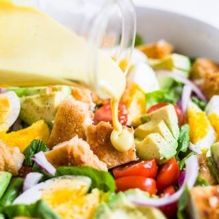 honey mustard dressing being poured on crispy chicken salad
