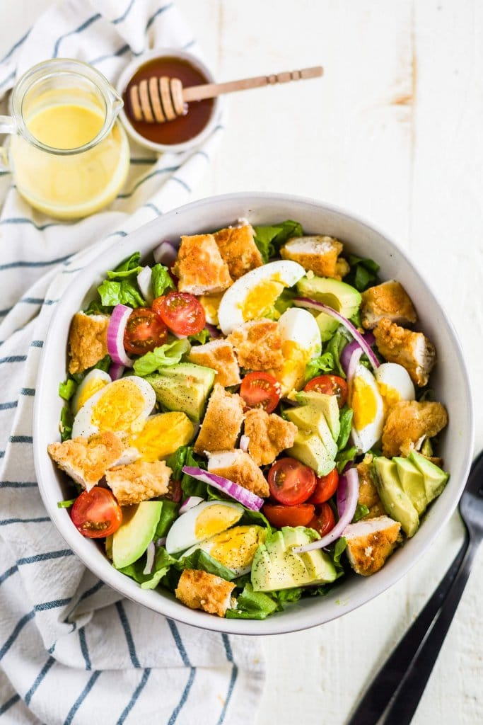 crispy chicken salad in a white bowl with a napkin