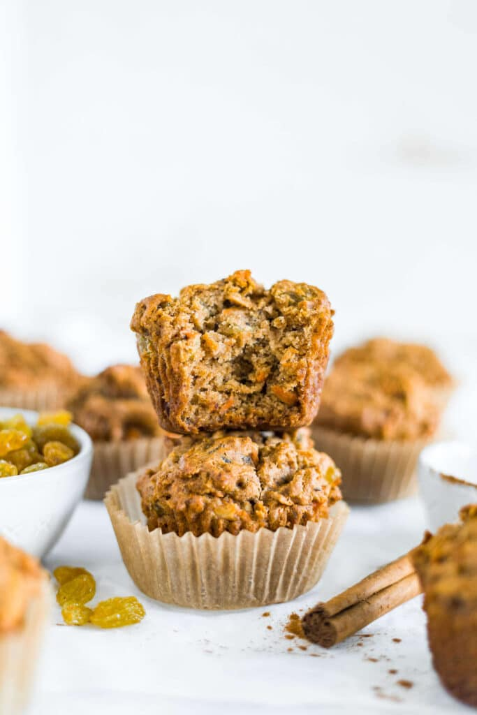 gluten free morning glory muffin stacked on top of another one with a bite taken out