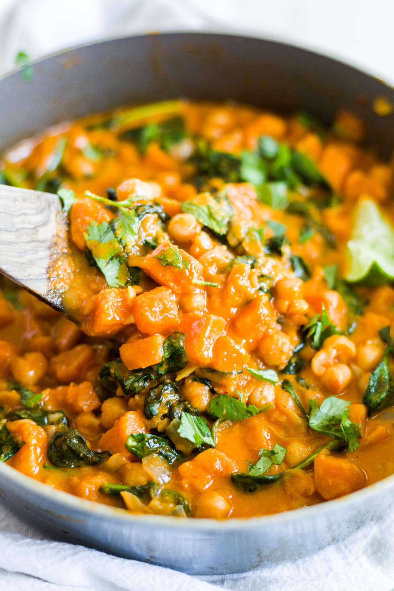 wooden spoon scooping out sweet potato curry from the pot
