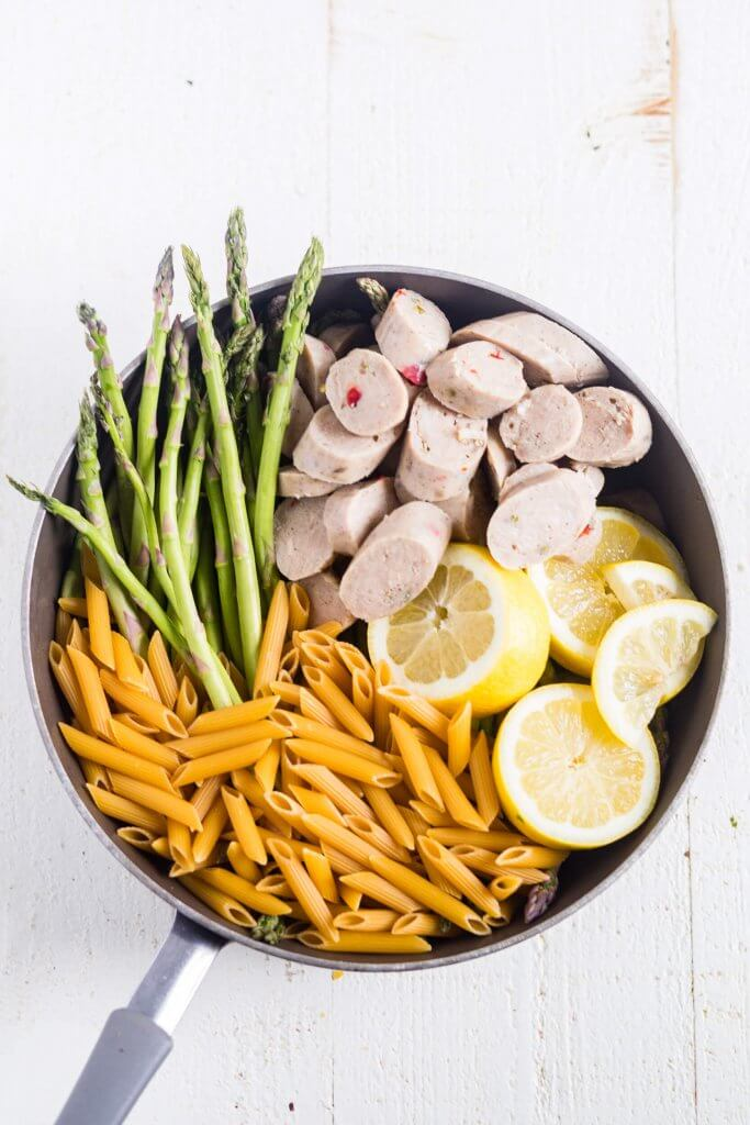 ingredients for lemon chicken asparagus pasta in a pot before being cooked