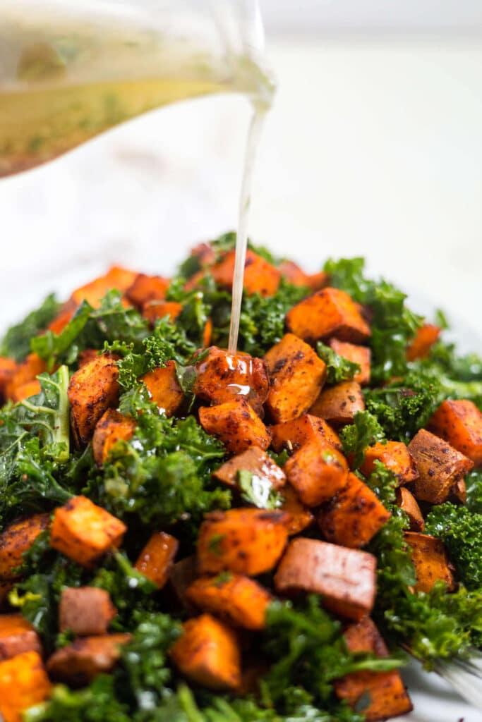cilantro vinaigrette pouring onto chipotle sweet potato salad