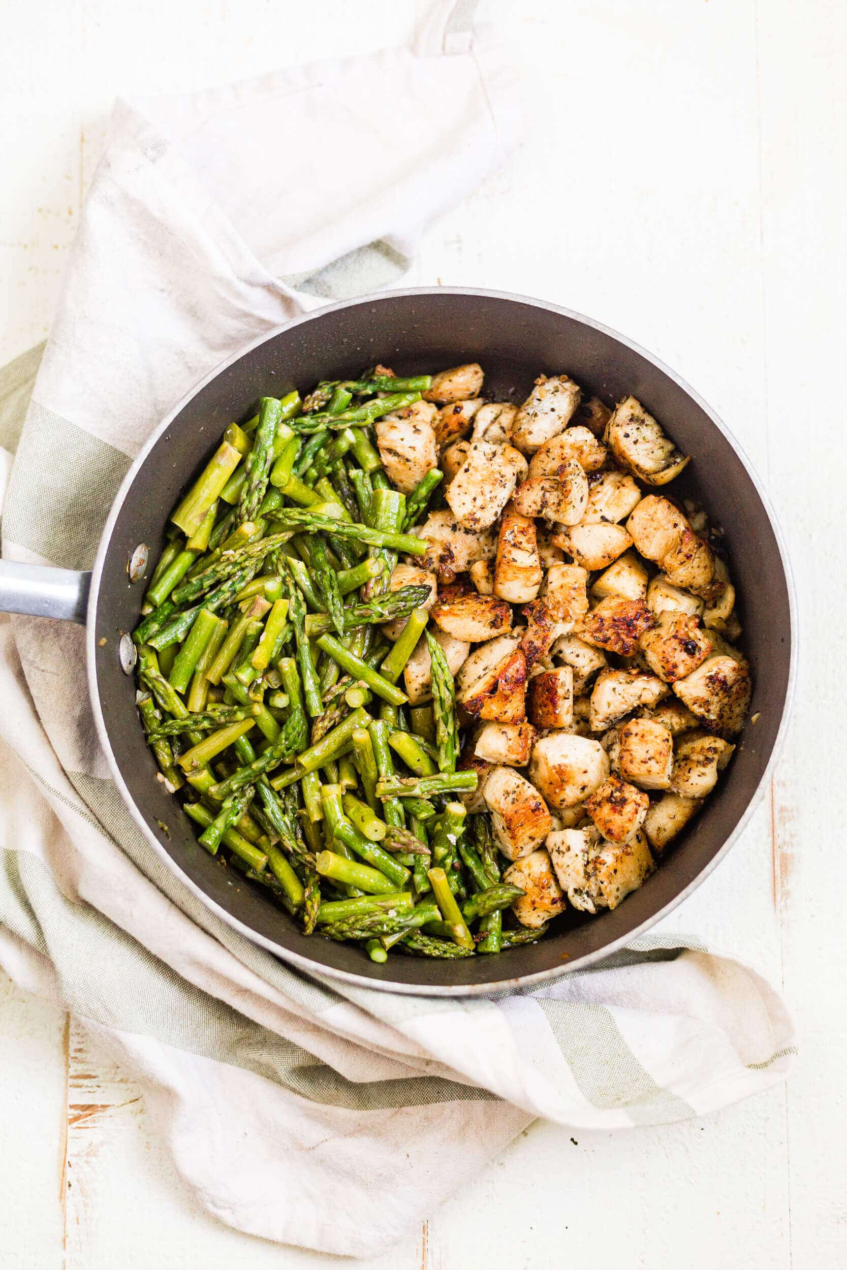 garlic chicken bites with asparagus in a saute pan