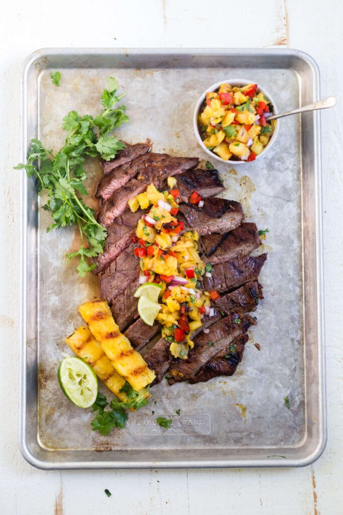 grilled flank steak sliced on a sheet pan with pineapple salsa