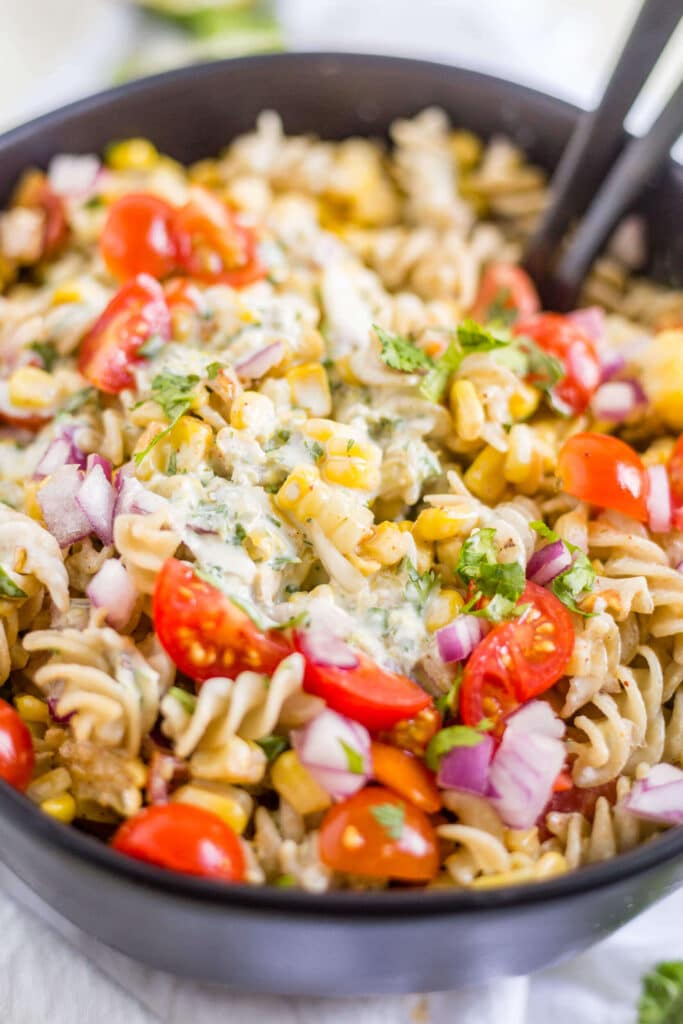 creamy jalapeno dressing on top of mexican street corn pasta salad in a black bowl with serving spoons