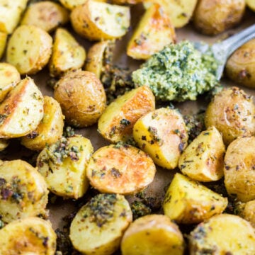 golden crispy potatoes on a sheet pan with pesto