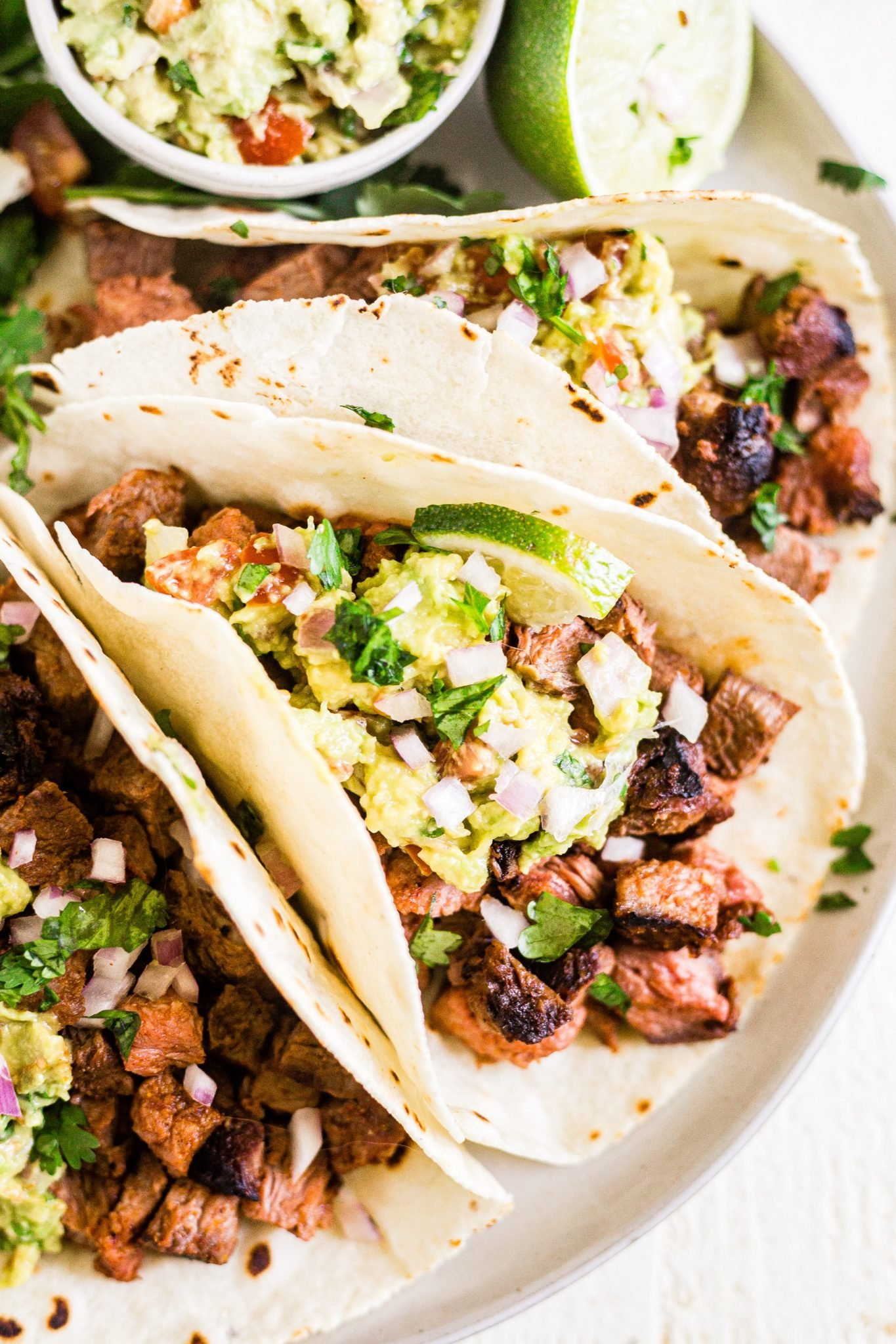three carne asada tacos on a white plate with fresh guacamole, onion and cilantro