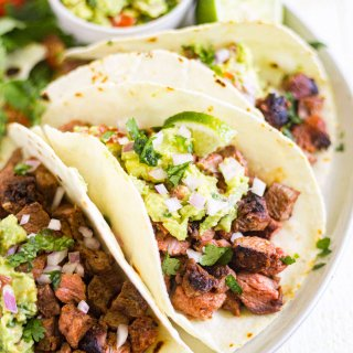 carne asada tacos on a white plate with guacamole