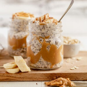 peanut butter overnight oats in a jar topped with sliced bananas and a spoon