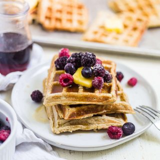 3 gluten free waffles on a white plate with butter, berries and syrup