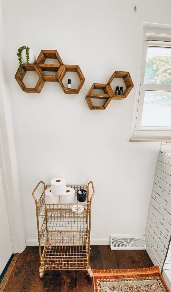 gold bar cart in the bathroom with hexagon shelving