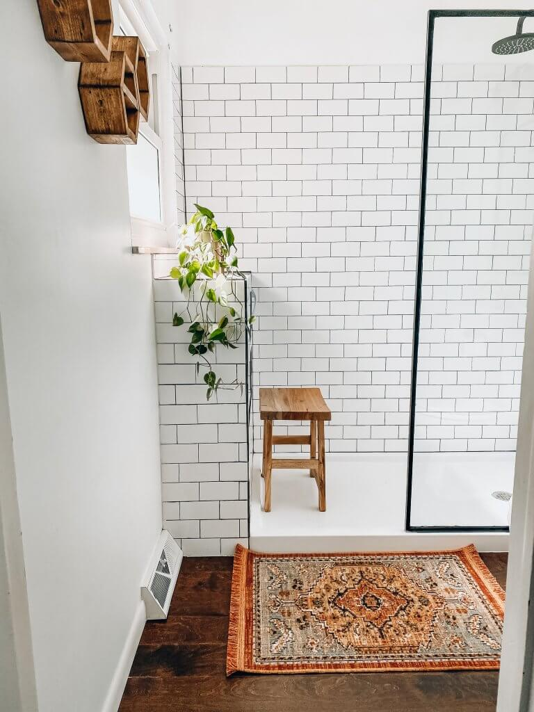 white subway tile shower with wood stool a plant and persian rug