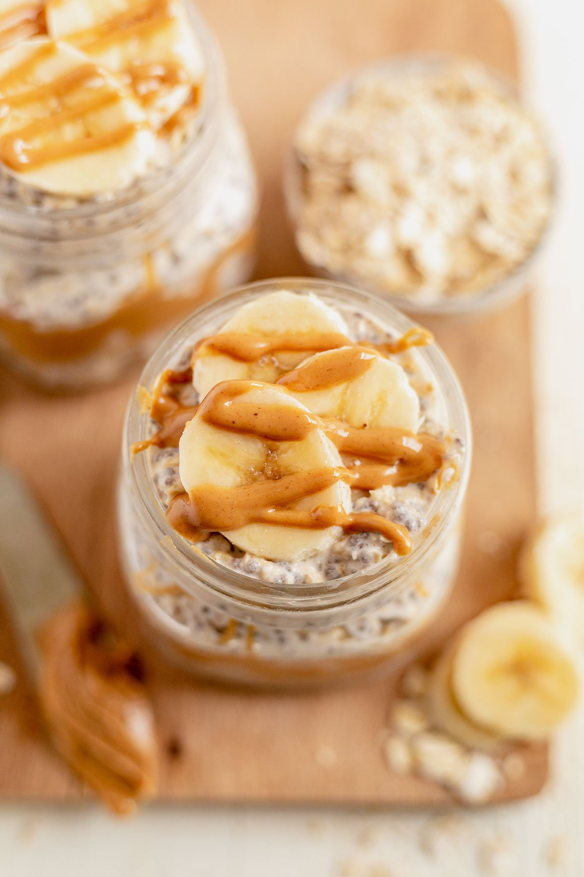 peanut butter chia overnight oats topped with sliced bananas and peanut butter drizzle