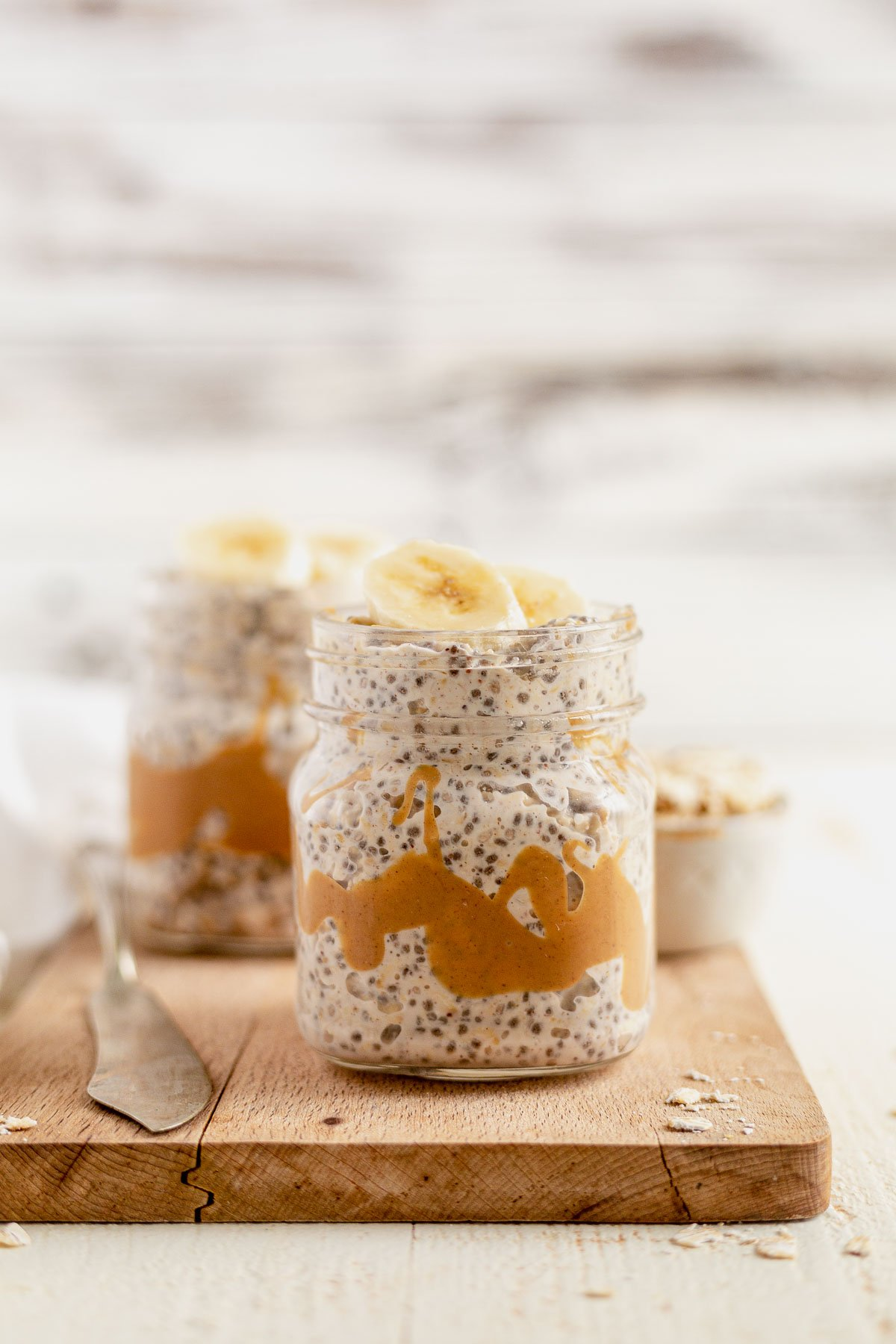 peanut butter overnight oats in a jar topped with bananas